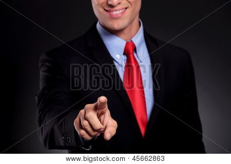 portrait of a young business man standing against a black background and selecting something or touching a button on an imaginary screen with a smile on his face
