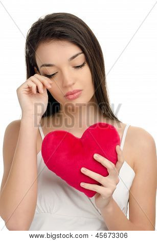 Beautiful upset brunette girl crying and holding a red heart. Concept of unhappy love on Valentine's Day. Isolated on white. poster