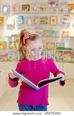 Little girl stands reading open book in book department at store