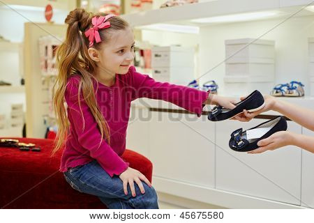 Little girl sitting on ottoman, takes pair of shoes from hands of seller