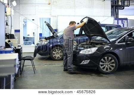 Mechanic in overalls opened hood of black car in small service station. poster