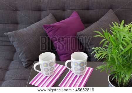 Sofa decorated with cushions two cups on a table and green plant. poster