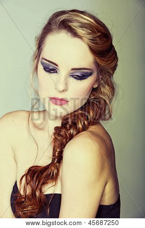 beautiful young woman with blond red hair in fishtail braid and dramatic eye makeup