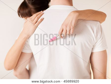 close up of woman with pregnancy test hugging man