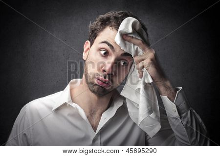 young man wipes sweat from his forehead with a handkerchief