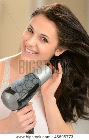 Happy girl blow drying her hair with blow dryer