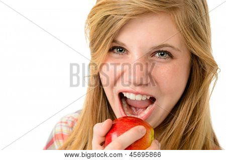 Teenage girl eating healthy apple isolated on white background