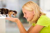 loving teen girl playing with pet kitten at home poster