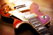 Red sunburst color single cutaway electric solid body guitar, on a old grungy wooden surface. Shallow depth of field. poster