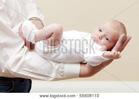 newborn baby girl lying on arm