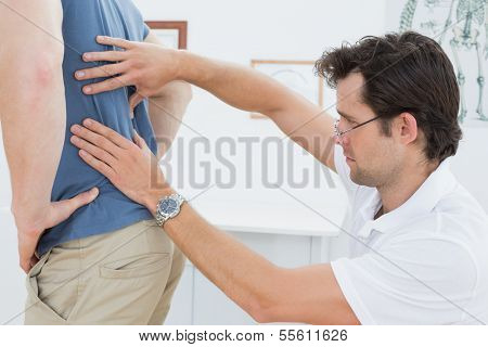 Side view close-up of a male physiotherapist examining mans back in the medical office