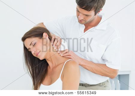 Male chiropractor massaging a young woman's neck in the medical office poster