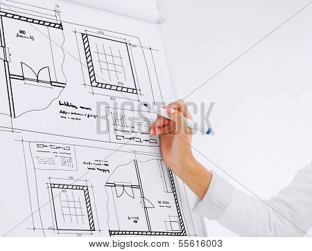 building, developing, office and architecture concept - businesswoman drawing bluepring on flip board in office poster