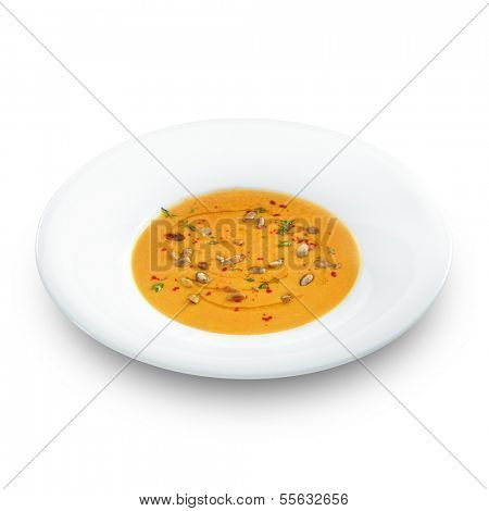 Hot healthy vegetarian pampkin cream soup with pampkin seeds in a round palate isolated on white.