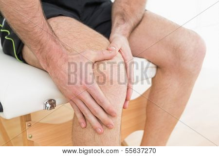 Close-up mid section of a young man with his hands on a painful knee while sitting on examination table poster
