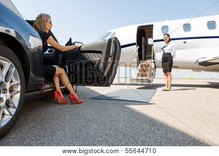 wealthy woman stepping out of car parked in front of private plane and airhostess poster