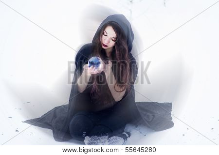 Witch or woman doing magic in black cloak with glass ball in white snow forest