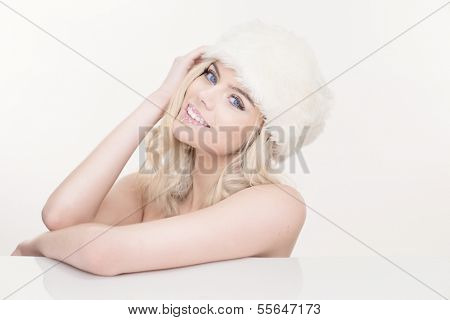 Beautiful naked blond girl with long curly hair and a lovely warm friendly smile in a white winter hat against a white background