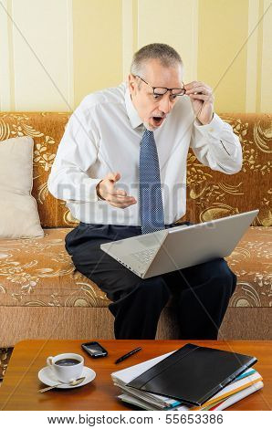 Surprised Senior Businessman With Computer