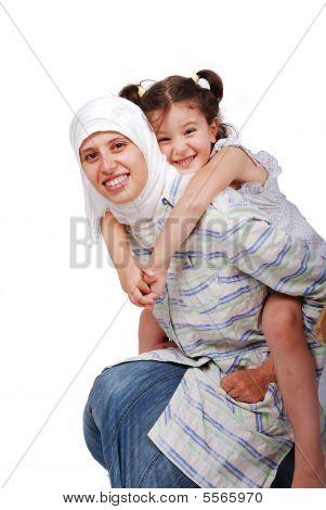 Молодой мусульманской женщины в традиционной одежде с маленькой девочкой на спине