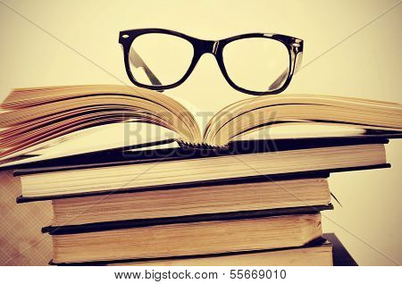 picture of a pile of books and eyeglasses, with a retro effect