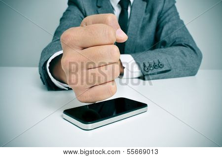 a businessman sitting in a desk hitting a smartphone with his fist