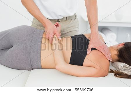 Male physiotherapist massaging woman's body in the medical office