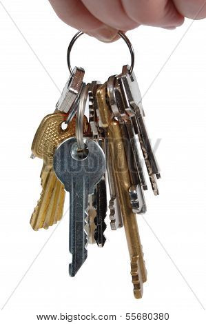 bunch of metal keys isolated on a white background. The human hand that holds the keys.