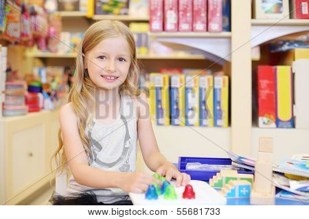 Little pretty girl with long blonde hair plays with toys in store.