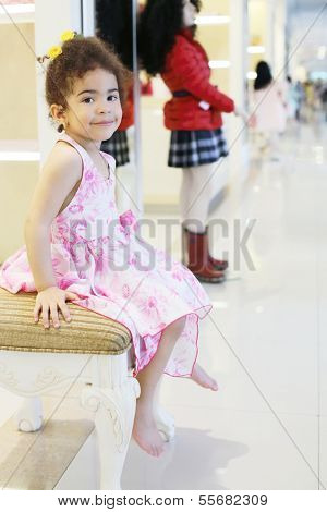 Little barefoot girl sits and smiles in children store with clothes for girls.