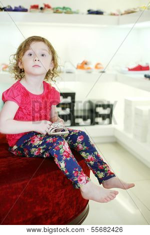 Little pretty girl sits on big pouf and holds sandal in children store.