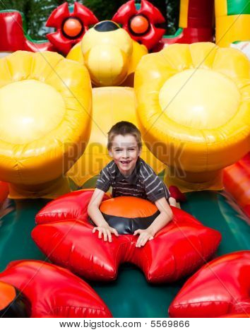 Boy In Inflatable Playground