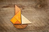 abstract picture of a sailing yacht built from seven tangram wooden pieces over a rustic  barn wood, artwork created by the photographer poster