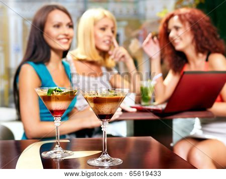 Two women at laptop drinking cocktail in a cafe.Sharpness on  glass