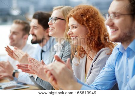 Photo of happy business people applauding at conference, focus on redhead female poster