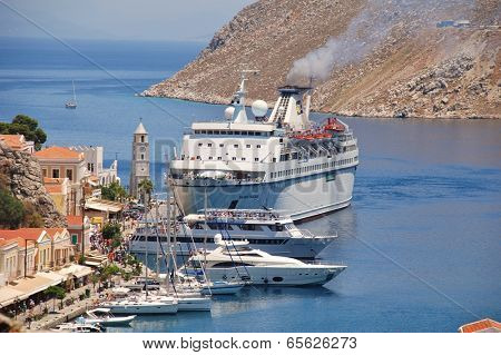 SYMI, GREECE - JUNE 23, 2011: Cyprus based cruise ship Salamis Filoxenia docks at Yialos harbour on the Greek island of Symi. The 157mtr long ship was built in 1975 in Finland.
