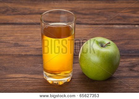 Glass of apple juice and green apple on wooden background
