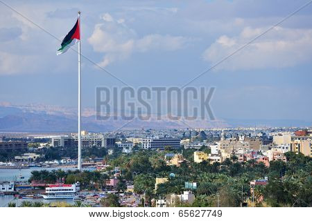 AQABA, JORDAN - MARCH 14, 2014: Flag of Jordan waving over the city. Aqaba has one of the highest growth rates in Jordan, with only 44% of the buildings being built before 1990