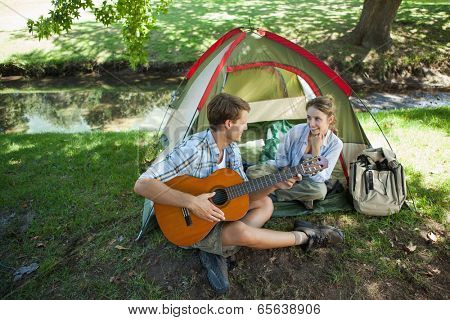 Cute man serenading his girlfriend on camping trip on a sunny day