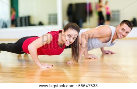 fitness, sport, training, gym and lifestyle concept - smiling couple doing push-ups in the gym
