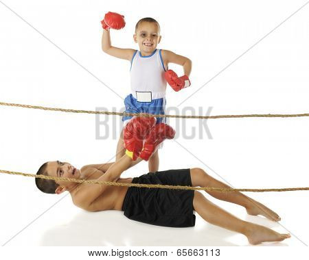 Two young brothers boxing behind ropes.  The preschooler (with a shiner) stands in victory with his foot on his big brother's chest, while the older one attempts to get up.  On a white background.