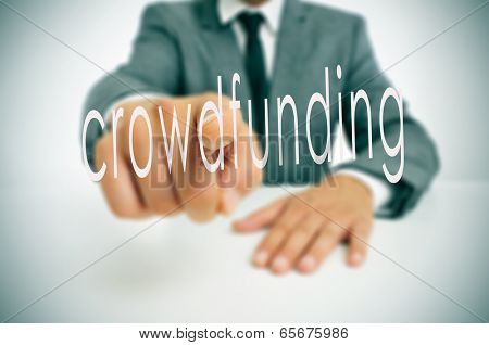 man wearing a suit sitting in a table pointing to the word crowdfunding written in the foreground