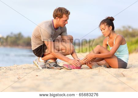 Injury - sports woman with twisted sprained ankle. Asian fitness female model sitting on beach sand getting help from Caucasian male touching her ankle.