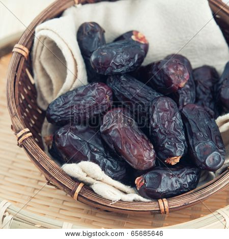Dates fruit or kurma. Pile of fresh dried date fruits in a basket.
