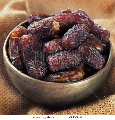 Pile of fresh dried date fruits in metal bowl. Dried date palm fruits or kurma, ramadan food which eaten in fasting month.