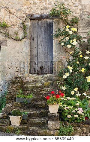 Close up of cottage with roses around door