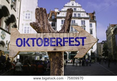 Oktoberfest wooden sign with a pub on background