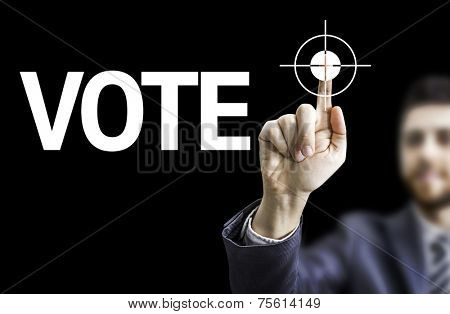 Business man pointing to black board with text: Vote