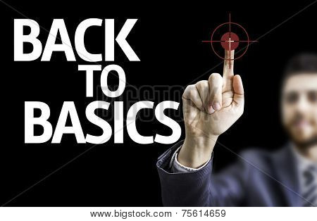 Business man pointing to black board with text: Back to Basics