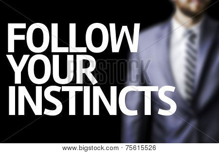 Follow your Instincts written on a board with a business man on background